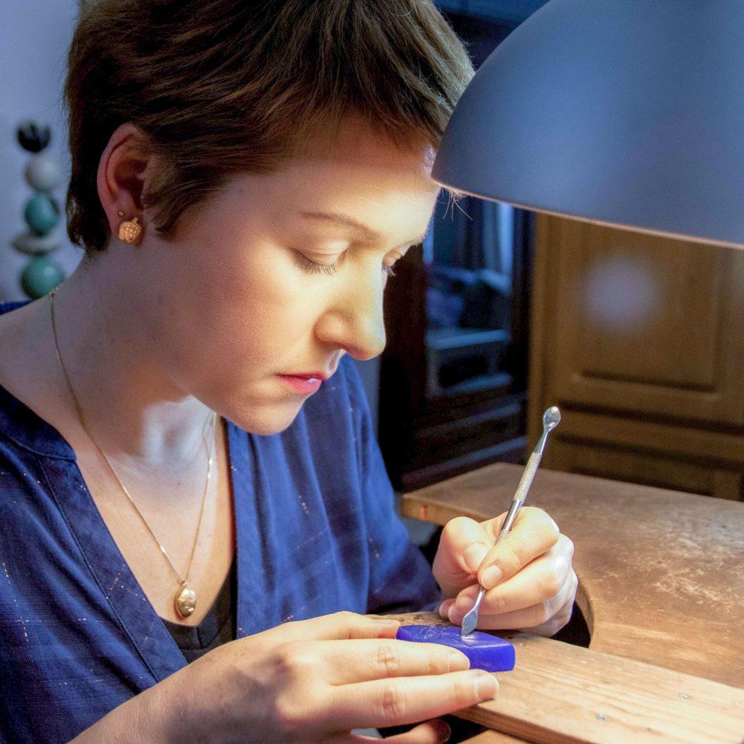 créatrice en train de sculpter un bijou dans de la cire de bijouterie