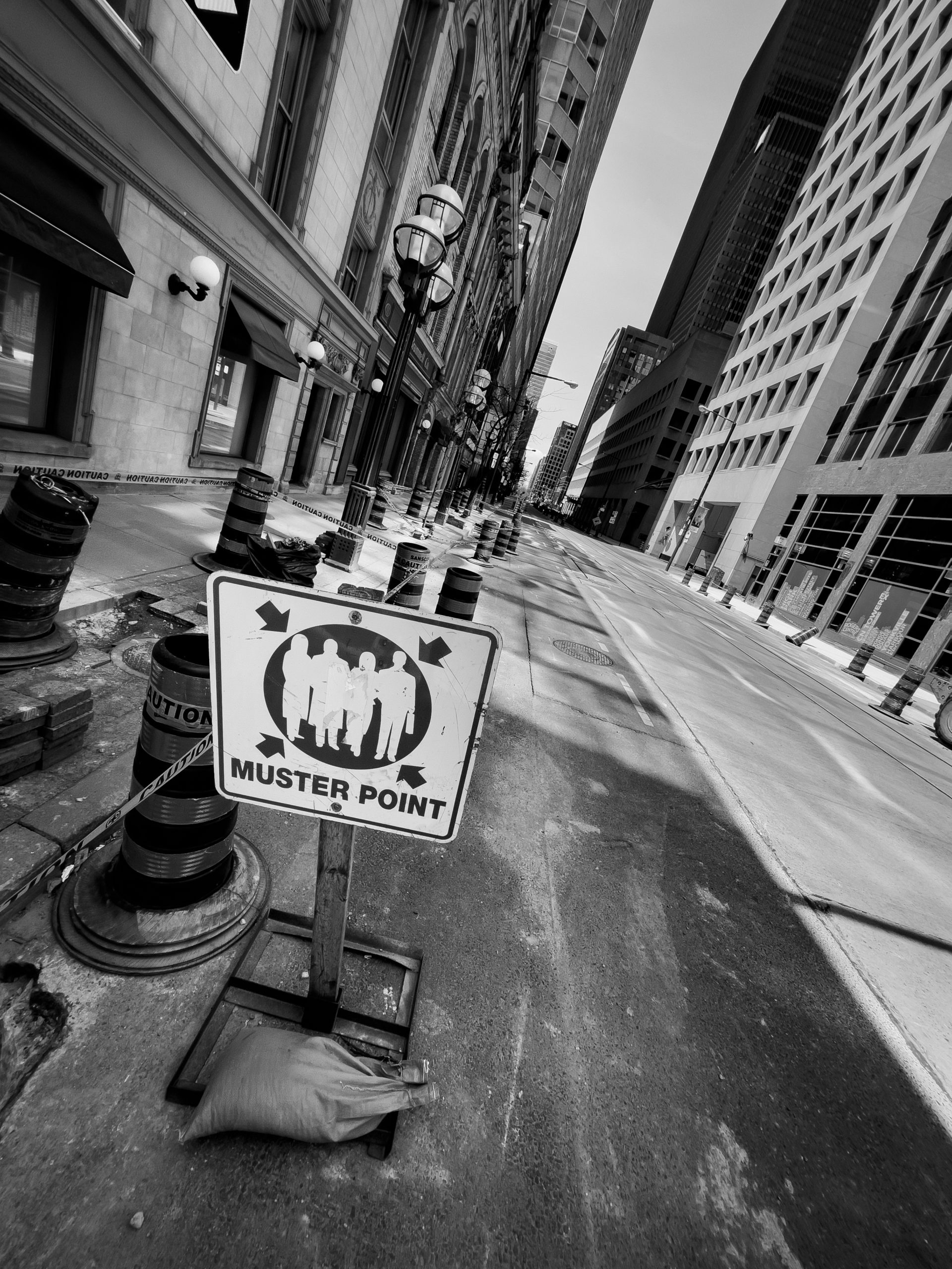 """A sign that says """"Muster Point"""" (with a silhouette of four persons) on a deserted downtown Toronto street. Photo is in black and white"""