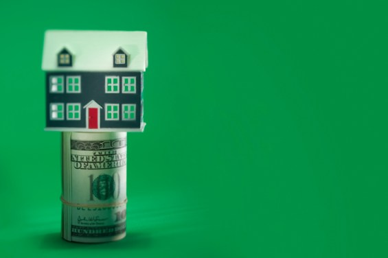 Roll of money with a miniature house