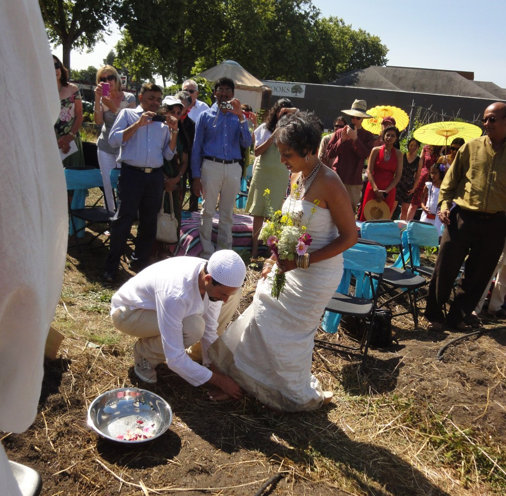 Micha'el BedarShah washes the feet of his bride, Aumatma, during the first wedding ceremony held at Urban Adamah, a Jewish educational farm in Berkeley, Calif., June 30, 2013. (Photos courtesy Micha'el BedarShah