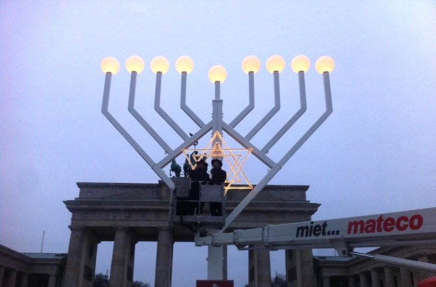 Rabbi Yehudah Teichtal, left, and a colleague testing out a Hanukkah menorah at Brandenburg Gate in Berlin, Dec. 22, 2016. (Courtesy of Teichtal)