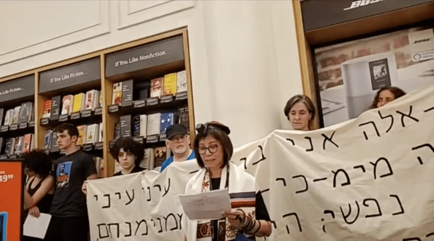 A demonstrator speaks at a Jewish protest against Amazon at one of the company's brick-and-mortar stores in New York City on Sunday, August 11. The protest was held on Tisha B'Av, a traditional Jewish day of mourning. Behind the speaker is a banner with a Hebrew quotation from the Book of Lamentations. (Screenshot from Facebook)