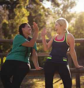 Two young women outdoors giving each other high fives for a great workout