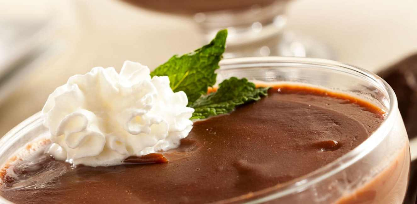 Fancy glass cup of chocolate, peanut butter pudding with a dollop of whipped cream and a mint sprig