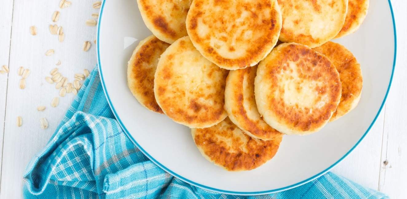 White plate with pile of pancakes on a blue tablecloth