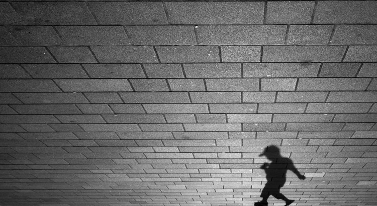 Child's shadow on brick wall