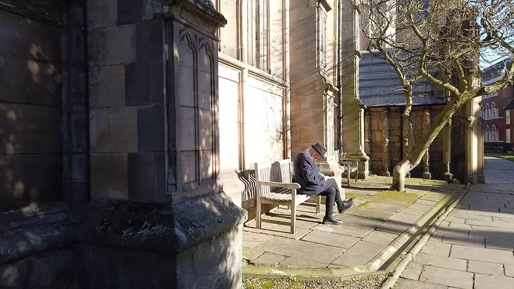 Man sitting on bench outside church