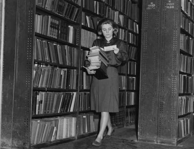 6. Bibliotecaria recogiendo libros reservados para sus lectores