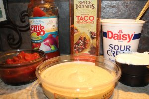 Collect the ingredients salsa, taco seasoning, hummus, and sour cream