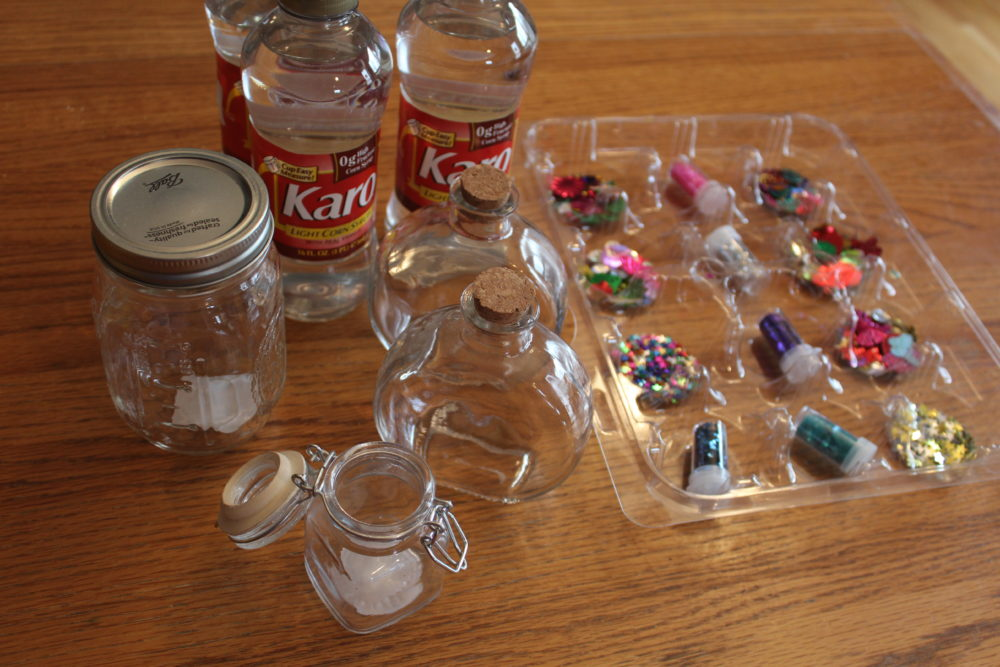 Supplies including jars with cork lids, sealing lids or mason jars, corn syrup, spangles