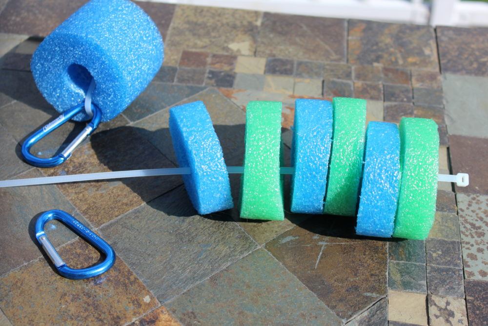 String noodle pieces onto zip tie. DIY Pool Noodle Goggle Holder Float. Pool time. Pool Noodle craft. Kids. Swimming pool. Swimming pool hack.