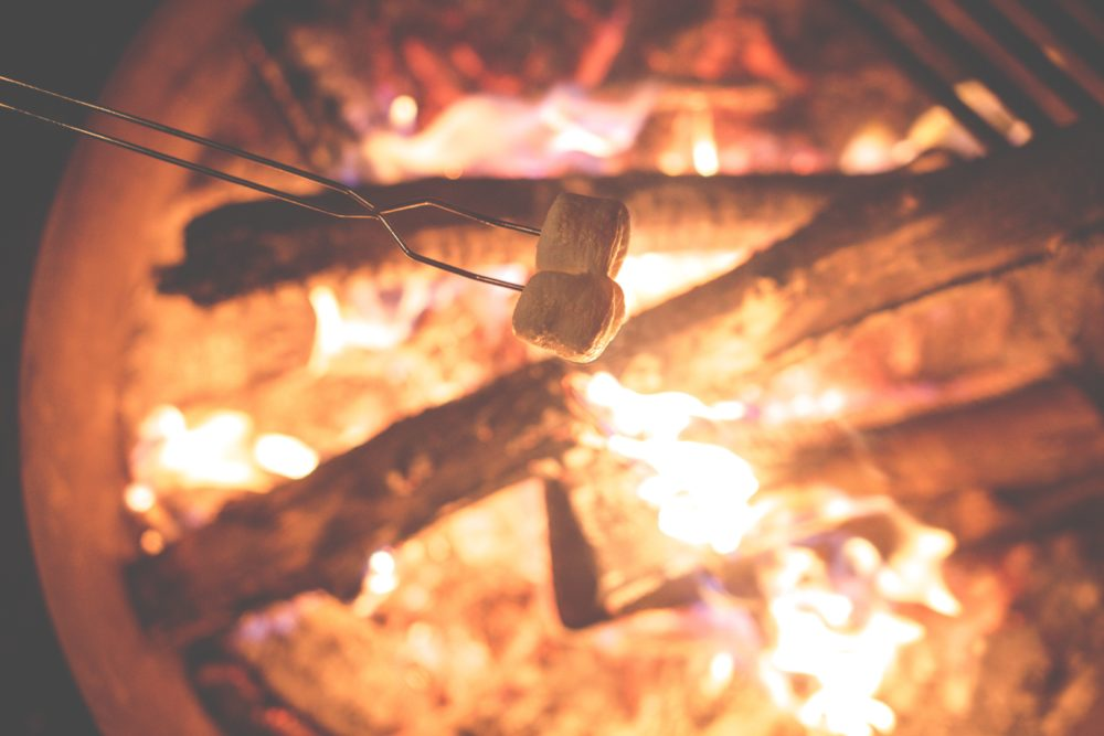 Family camping essentials. Cooking smores over the campfire with roasting stick.