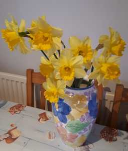 Image of daffodils in a colourful vase on a table
