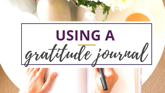 using a gratitude journal to write down thoughts with a cup of tea nearby