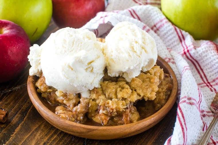 Apple Crisp on brown plate with apples in background