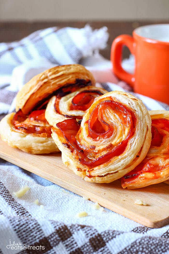 Puff Pastry Appetizers - Bacon Pinwheels with Cheddar sitting on a wooden cutting board.