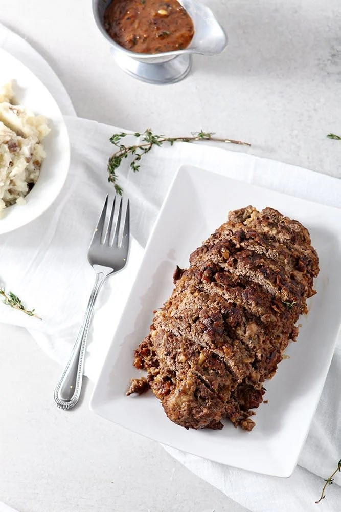 French Onion Meatloaf, sitting on a white platter, sliced and ready for eating