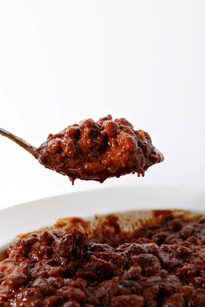 A spoon scoops out a serving of Pressure Cooker Baked Beans from a white bowl