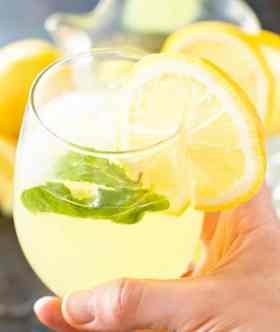 Hand Holding Sparkling Mint Lemonade in Glass