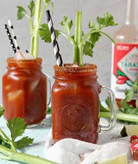Two BBQ Bloody Marys sit next to each other with Bloody Mary Mix in the background, surrounded by limes and celery stalks