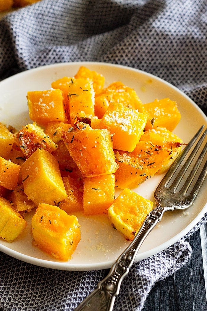 Oven roasted butternut squash on a white plate with fork.