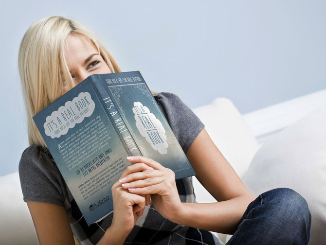 Tilt view close-up of woman sitting on white couch and giggling as she hold a book up to her face. Horizontal format.