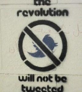 """Hier ist ein Graffito an einer Hauswand zu sehen, darauf steht """"The revolution will not be tweeted"""""""