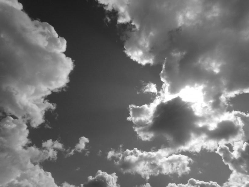 Hier ist ein Bild des Himmels zu sehen, die Sonne versteckt sich (noch halb sichtbar) hinter einer großen Kumuluswolke