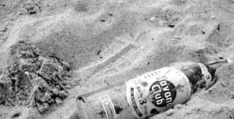 Hier ist eine leere Flasche Rum im Sand eines Strandes zu sehen