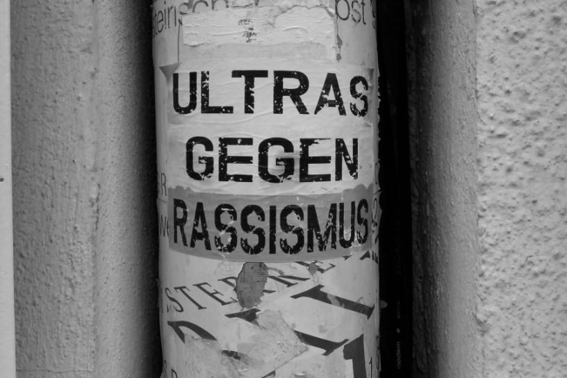 """Hier ist ein alter, halb abgepellter Aufkleber auf einem Regenrohr in Graz zu sehen. Die Aufschrift lautet """"Ultras gegen Rassismus"""""""