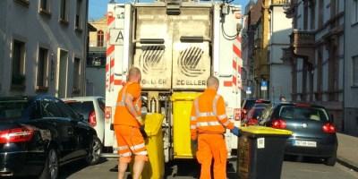 Hier ist ein Bild eines Müllwagens von hinten zu sehen. Zwei Mitarbeiter der Stadt sind gerade dabei, die gelben Tonnen in die Vorrichtungen einzuhängen.