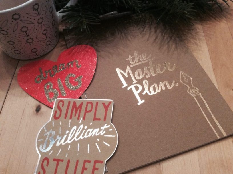 """Auf einem Tisch liegt ein Notizbuch, auf dem """"The Masterplan"""" steht. Daneben einige Sticker und eine Teetasse."""