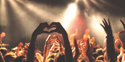 Hier ist ein Bild einer Menge Menschen vor einer Bühne zu sehen. Vorne ist Scheinwerferlicht, und die von hinten fotografierten Menschen halten die Arme hoch. Eine Person führt die Hände zu einem Herz zusammen.