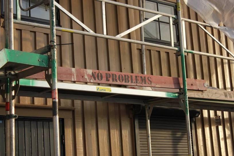 """Hier ist ein Bild von einem Baugerüst um ein Haus zu sehen. Auf einer der Bretter auf dem Gerüst steht """"no Problems""""."""