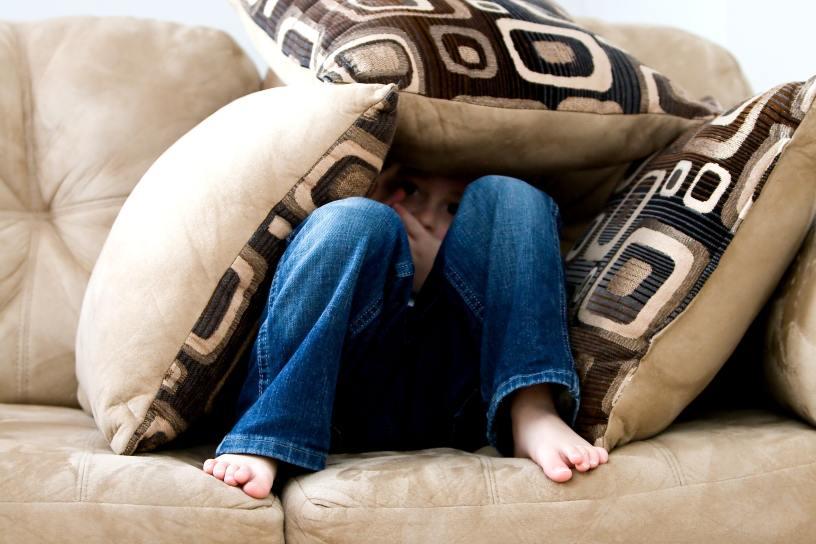 Junge auf der Couch, der sich mit Kissen bedeckt