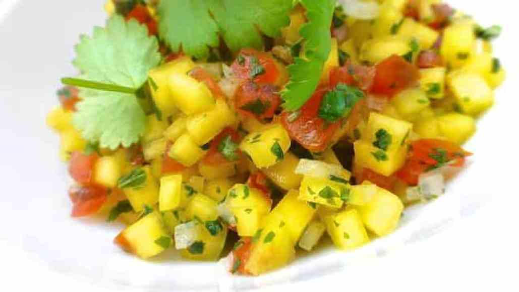 Mango salsa: a fresh and crunchy fiesta appetizer! The recipe is truly simplistic: mango, tomato, onion, lime and fresh cilantro.