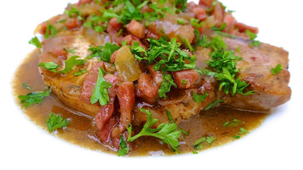 Succulent baked pork chops in beer sauce with crunchy bacon bits and soft onion... No need to say how fantastic this recipe tastes!