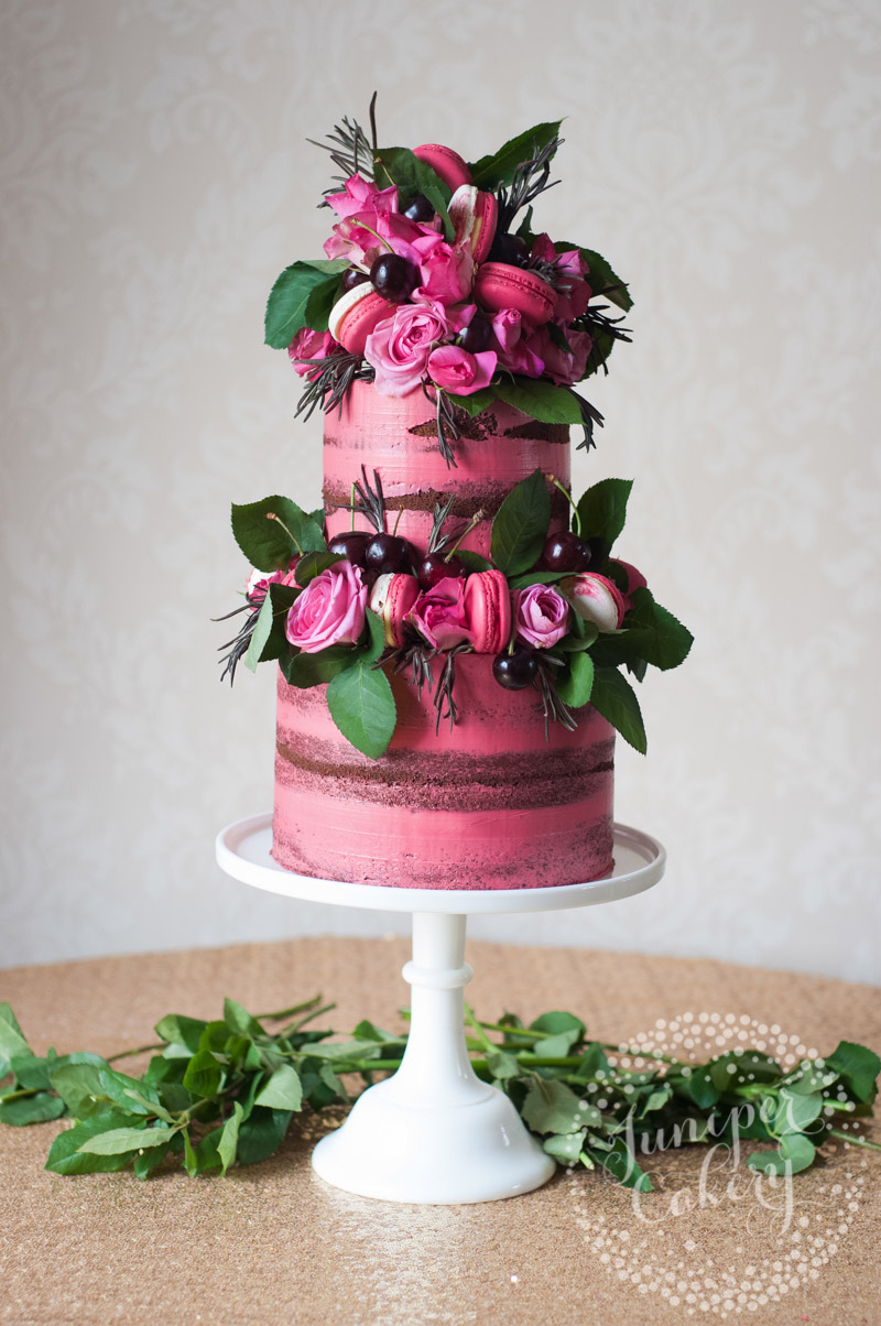 Pretty pink naked cake with cherries, macarons and roses by Juniper Cakery
