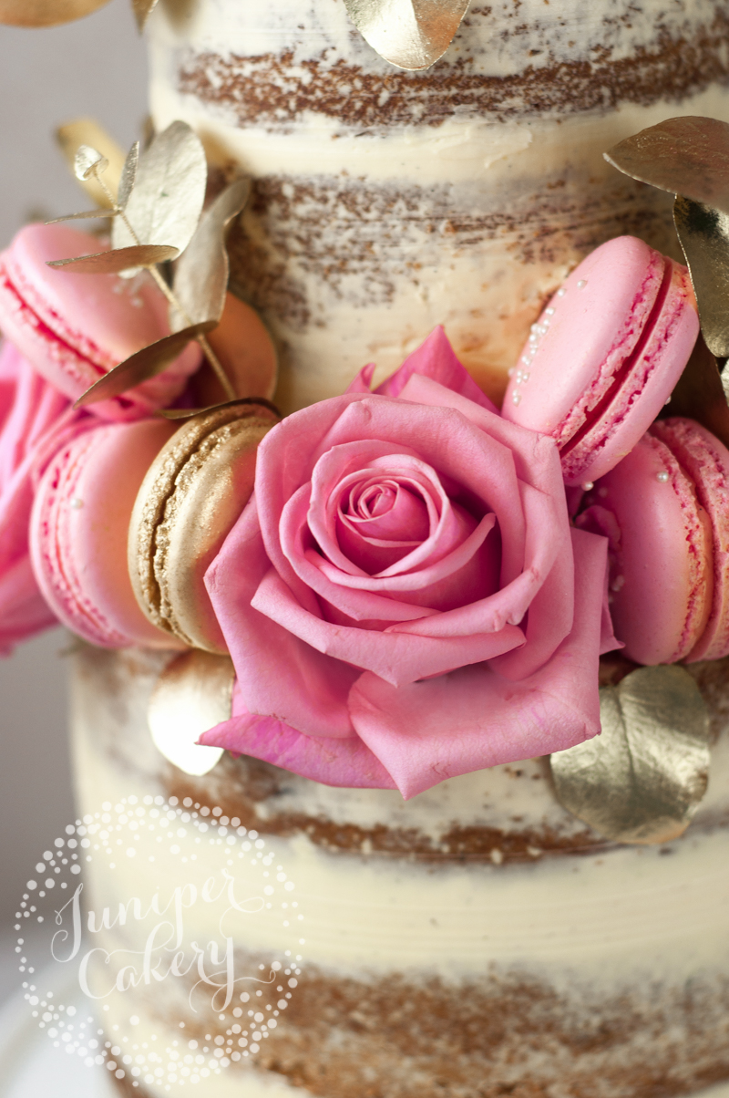 Pretty pink roses on a pink and gold naked cake by Juniper Cakery