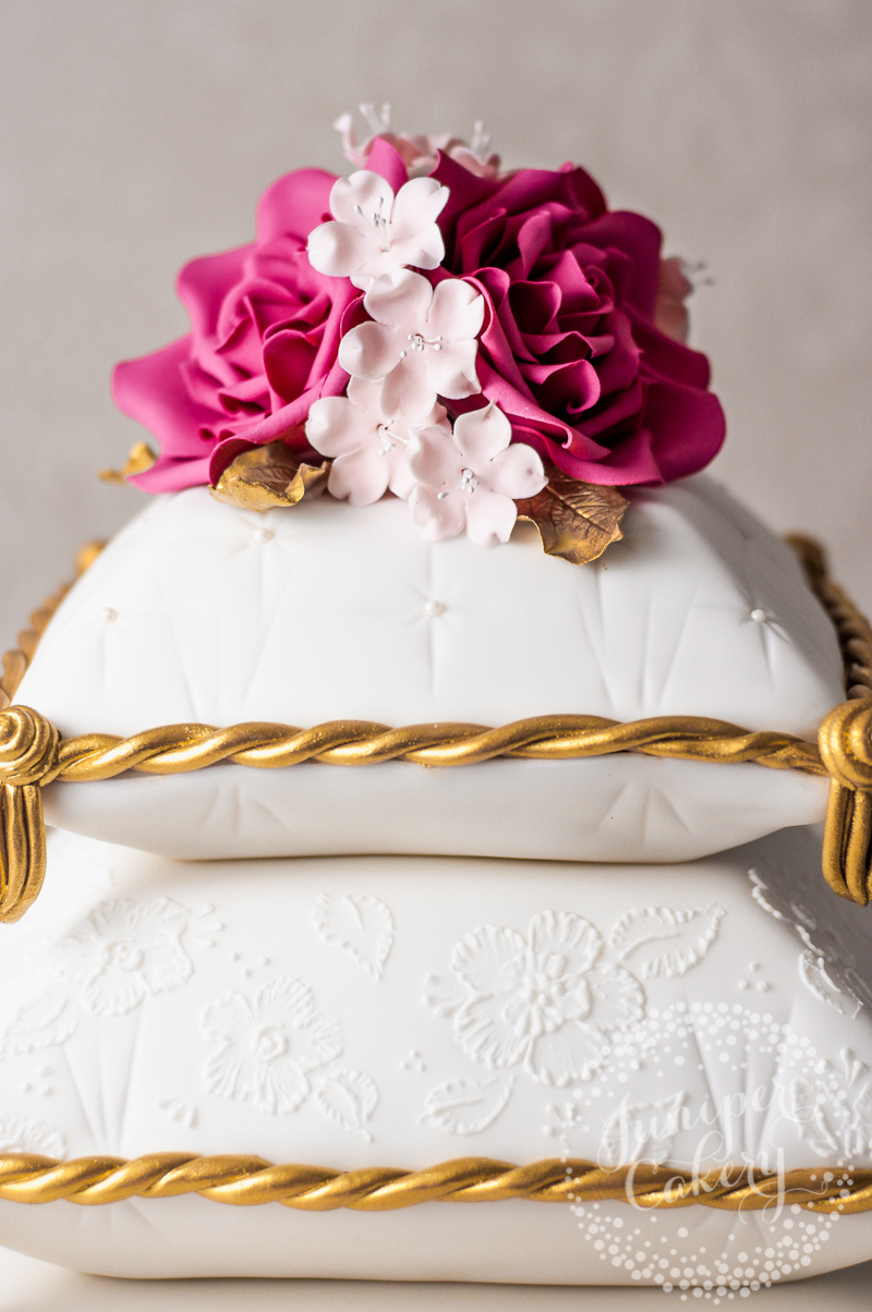 Pink rose and cherry blossom adorned pillow cake by Juniper Cakery