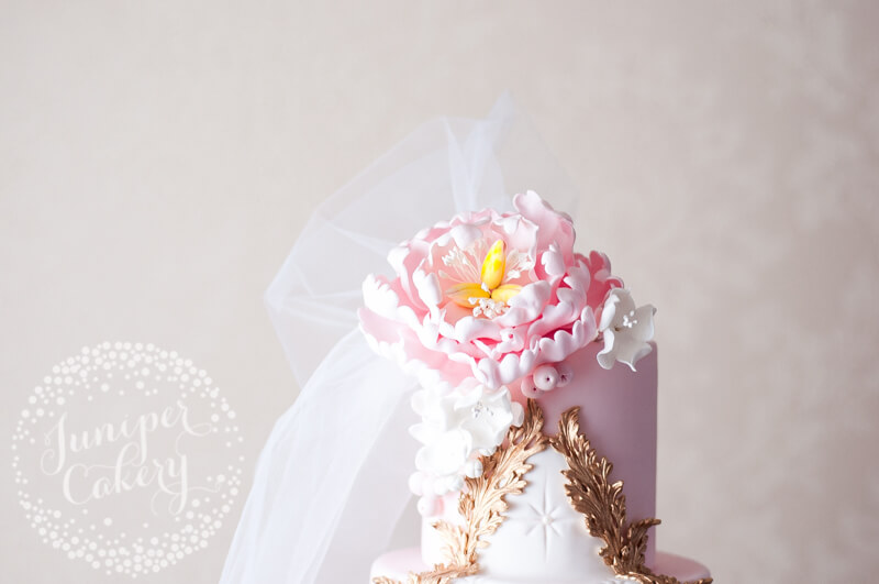 Pale pink Rococo wedding cake with 24k acanthus leaf frame by Juniper Cakery