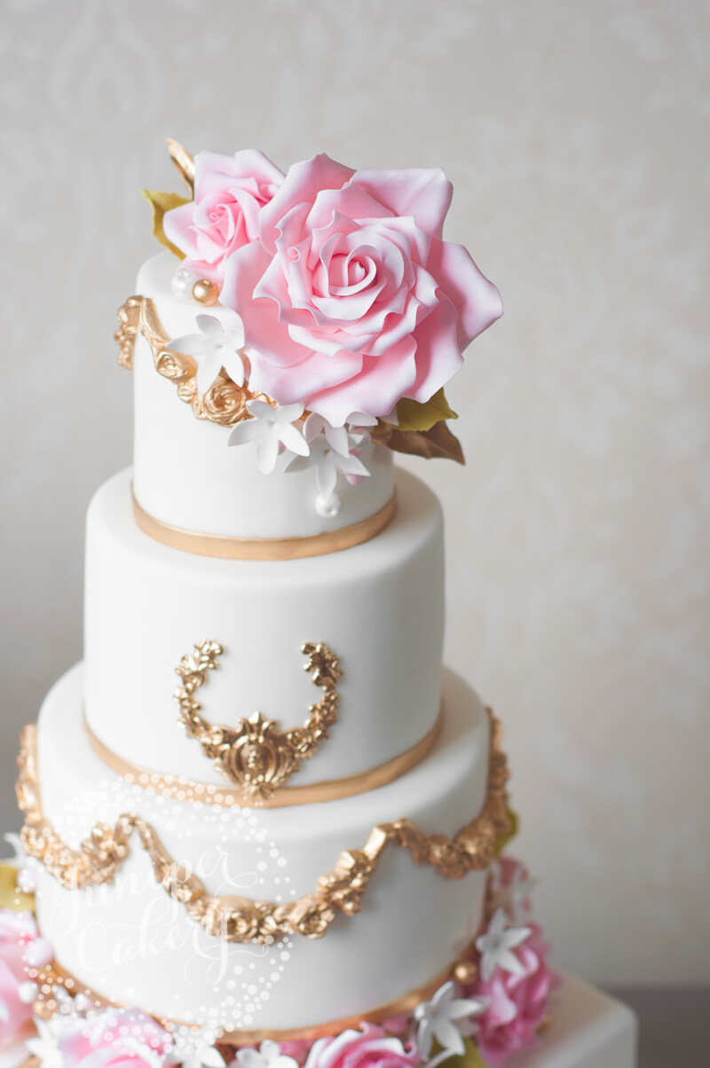 Gold painted wedding cake with oversized pink roses by Juniper ...