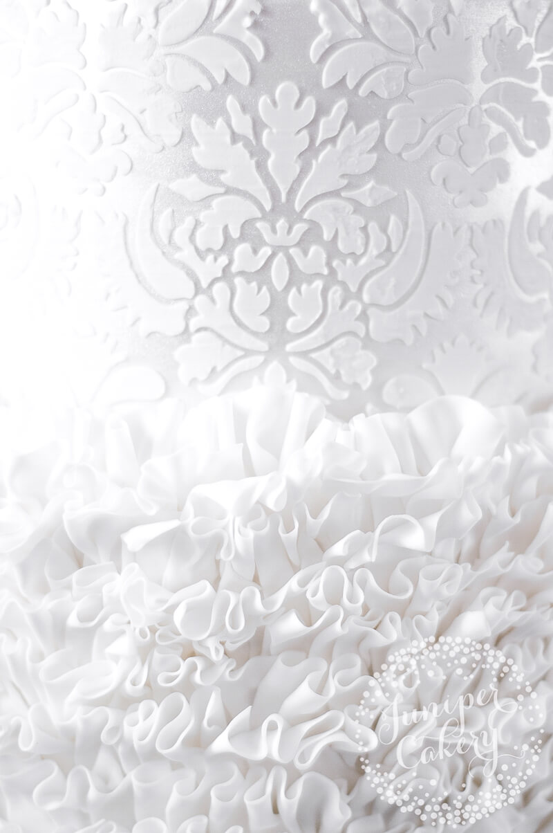 White damask, lustre and fondant ruffle detail on a wedding cake by Juniper Cakery