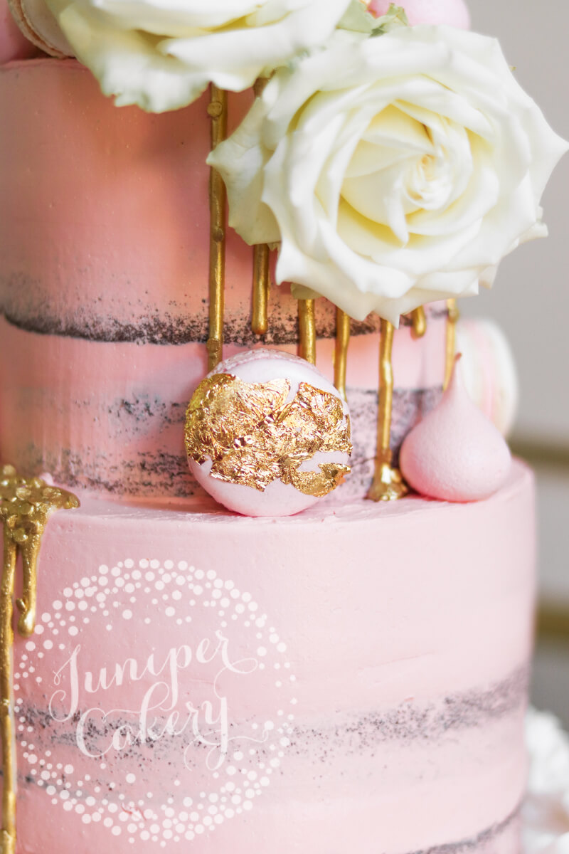 Gold leaf macaron on a blush pink wedding cake by Juniper Cakery