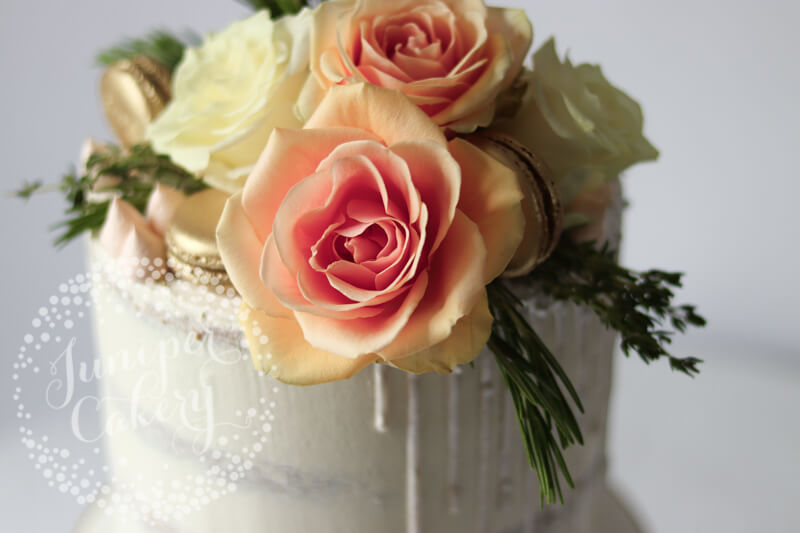 Fresh roses on a white semi-naked cake by Juniper Cakery