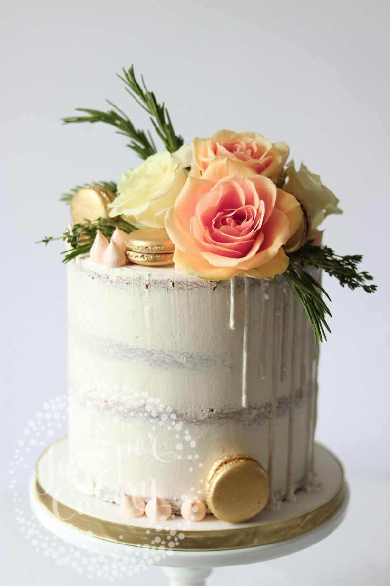 White semi-naked cake with gold macarons, peach ombré roses, rosemary sprigs, sugar pearls and piped buttercream kisses by Juniper Cakery