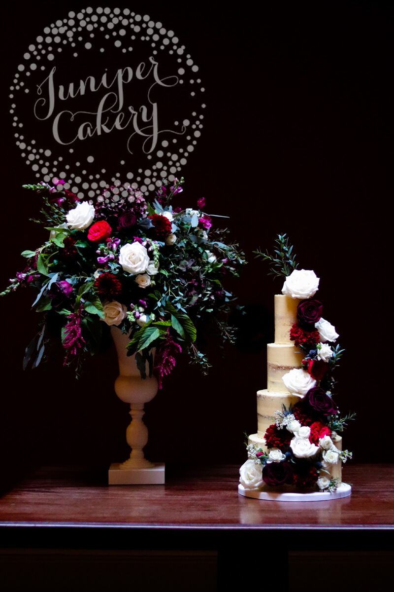 Beautiful berry and navy semi-naked wedding cake by Juniper Cakery