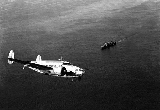 A Lockheed Hudson Mk I bomber and reconnaissance aircraft flying over a minesweeper, August 15th, 1940.