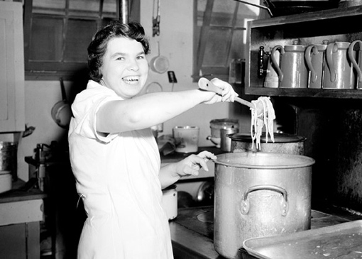 Mrs. E. Elliott cooking spaghetti in the kitchens of No 3 Service Flying Training School (SFTS), Calgary.
