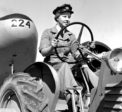 Aircraftswoman 2nd Class Laura Bagby towing a trainer aircraft with a tractor, No 3 Service Flying Training School (SFTS), Calgary, Alberta.